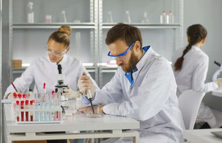 Portrait of three scientists doing research studying substances in modern laboratory, focus on young man wearing protective glasses, selective focus of genetic consultant doing dna test. Standard-Bild