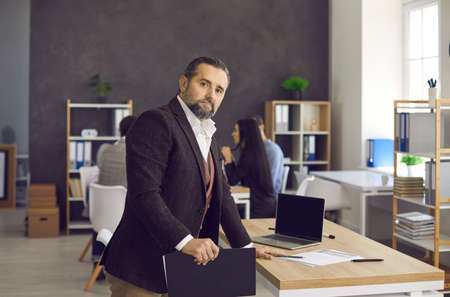 Portrait of serious elegant good-looking senior businessman and professional business executive. Handsome mature Caucasian man in suit looking at camera standing near desk in modern office workspace Standard-Bild