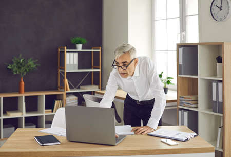 Concentrated senior European businessman while working with laptop computer in office, office lifestyle concept. A man in a white shirt and glasses at a laptop Standard-Bild