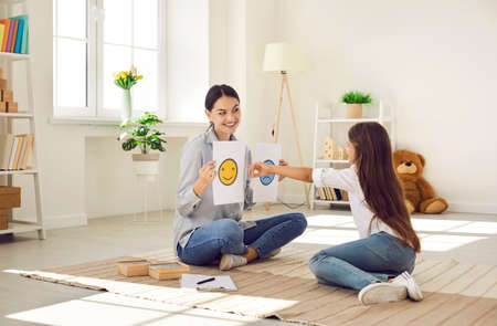 Professional childrens psychologist talking to little kid about emotions. Girl chooses happy smiley emoticon from two EQ cards that female therapist shows her during interview appointment meeting