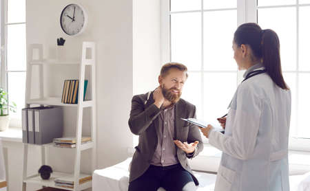 Male patient talking to doctor about pain in the nape of his neck. Female general practitioner listening to man who cant stretch stiff tight injured neck due to severe fibromyalgia or muscle strain