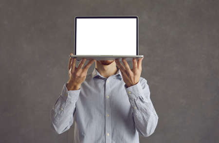 Unrecognizable man holding his laptop with white blank screen at face height while standing on gray background. Young businessman hides his face behind computer showing copy space. Banner Advertising. Standard-Bild