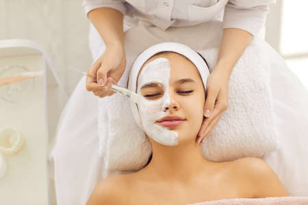 Top view of cosmetologist do facial mask for healthy glowing skin for smiling female client. Dermatologist make beauty procedures for woman patient in aesthetic medical clinic. Cosmetology concept.