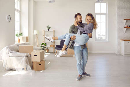 Happy young married couple on threshold of new life. Newlyweds having fun in big new home. Strong man carrying his woman in arms in newly bought modern spacious unfurnished house. Real estate concept Standard-Bild