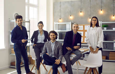 A group of successful business teams of senior and young age, in a modern minimalist office, looking at the camera and smiling. Successful team. Successful business concept Standard-Bild