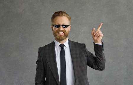 Happy smiling successful adult caucasian businessman corporate leader in formal suit and thug life sunglasses pointing aside at grey copy space advertising something. Studio headshot portrait Standard-Bild