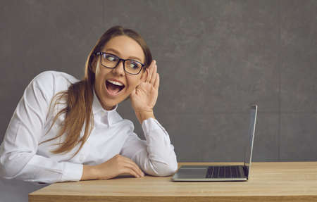 Young woman sitting near a laptop trying to eavesdrop on something by putting her hand to her ear. Side view of a woman in glasses and shirt is happy to overhear secret gossip. Concept of deafness. Standard-Bild