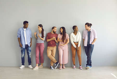 Diverse people leaning on studio background and talking. Full body length indoor group shot of happy young men and women making friends, sharing and listening to opinions and finding common grounds