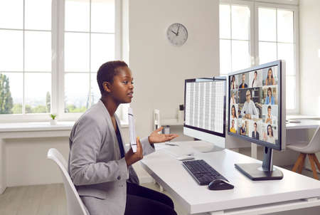 Woman making presentation in online business network meeting. Young black lady sitting at work desk in office, looking at desktop computer screen, showing data sheet and talking to team of colleagues