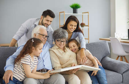 Happy big family grandparents with twin granddaughters and their parents browse the family photo album and share happy memories. Family gathered together in the living room. Family connection concept.