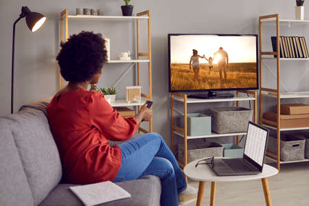 Adult woman takes break from working on laptop and watches movie on TV. Happy black lady resting on sofa in living room interior at home and enjoying favorite show on television set with big screen Standard-Bild