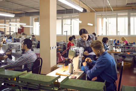 People working in a big workshop room at a shoe factory. Male and female workers sitting at tables with industrial sewing machines and making new footwear details. Manufacturing industry concept Standard-Bild