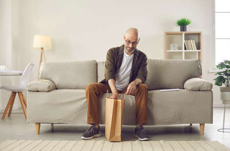 Customer opens brown craft paper delivery bag. Bald middle aged man sitting on sofa in modern interior at home and unpacking things he ordered online. Online shopping and express delivery concept Standard-Bild