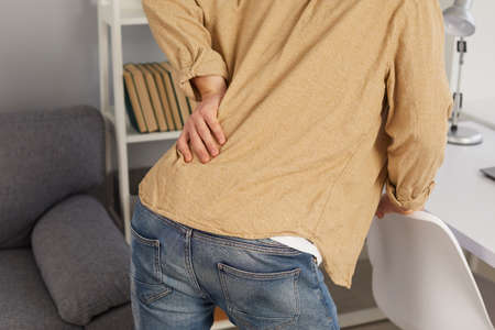 Close up back view of employee touch lower back suffer from muscular strain working in incorrect posture. Unwell tired man struggle with muscle spasm from office siting job. Sedentary lifestyle.