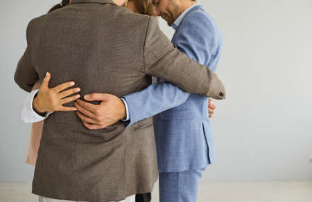 Close up of diverse employees colleagues hug engaged in teambuilding activity in office. Multiracial businesspeople on grey background show unity, have team motivational training at workplace.