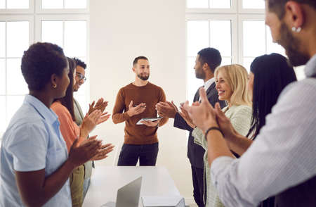 Excited businesspeople applaud successful male speaker or trainer for presentation or lesson at meeting. Happy employees clap hands show appreciation acknowledgement to team leader for speech.