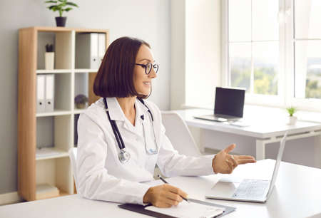 Happy woman who works as doctor sitting at office desk, looking at laptop computer screen, giving online telemedicine consultation, having conversation with patient, discussing treatment and smiling