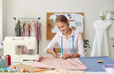 Happy young Caucasian woman designer create garment clothing in atelier or fashion studio. Smiling seamstress or tailor work design clothing in workshop. Style, dressmaking, hobby concept.