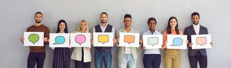 Different multiracial multiethnic people holding various cards and sheets of paper with pictures of colorful mockup chat message bubble icons. Concept of communication via messengers and social media Standard-Bild