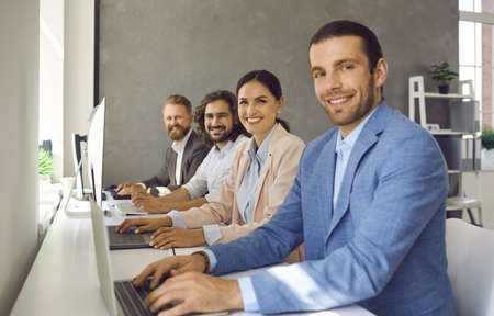 Portrait of confident team working together sitting in row next to each other in office. Side view of business people sitting in front of laptops and looking at camera smiling. Workspace concept.