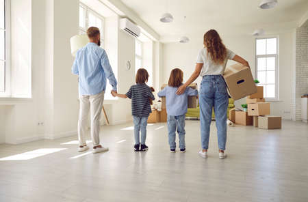 Family standing in empty unfurnished spacious living room, rear view, from behind. Mom, dad and kids carrying and unpacking boxes together while moving into house or apartment. Buying new home concept