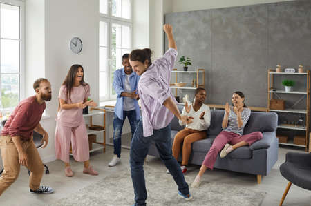 Happy positive diverse college students and friends dancing and having fun at a party at home. Mixed race group of cheerful people watching young man dance, applauding and enjoying good time together Standard-Bild