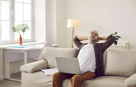 Tired man employee worker fall asleep on sofa working online on laptop at home. Exhausted middle-aged male doze sleep on couch in living room, distracted from computer job. Overwork concept. Standard-Bild