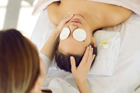Beauty and relaxation. Young calm female client enjoys relaxing face and head massage in spa or in beauticians office. Top view close up of woman relaxing lying on couch with cotton pads on her eyes.