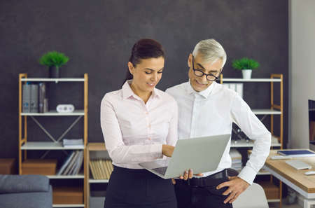 Two happy people standing and looking at something interesting on computer screen. Young business assistant office intern girl holding modern laptop and showing senior man new stuff shes working on
