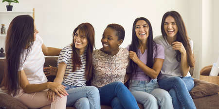 Group of happy multiracial female friends sitting on sofa, telling funny jokes and laughing. Multiethnic young women spending time at home, talking, sharing positive emotions and having fun together Standard-Bild