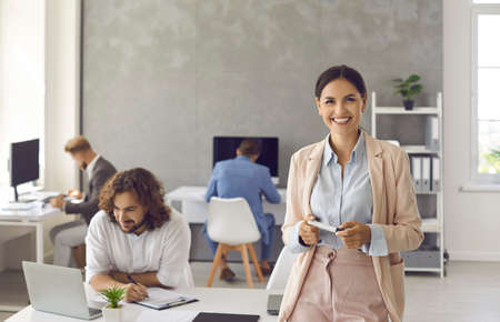 Portrait of happy positive businesswoman at work. Cheerful good looking young woman in suit standing in office, holding marker, looking at camera and smiling with employees working in background Standard-Bild
