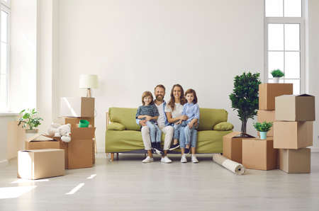Happy family in their new home on moving day. Portrait of mum, dad and kids sitting on sofa in new house or apartment full of unpacked cardboard boxes. Real estate, mortgage, buying property concept Standard-Bild