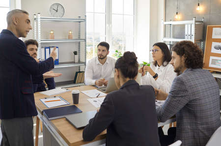 Businessman explaining new business ideas to colleagues sitting at briefing desk. Businesspeople discussing at conference room. Business meeting, teamwork and brainstorming concept Standard-Bild