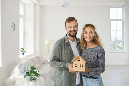 Portrait of happy young couple standing in empty new home, holding small miniature model of wooden house in hands, smiling and looking at camera. Real estate, mortgage, buying property, safety concept Standard-Bild