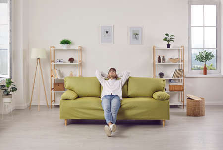 Young apartment owner spending free time on comfy couch at home. Happy relaxed man enjoying quiet leisure while sitting on green sofa in cosy living room interior. People, lifestyle, comfort concept Standard-Bild