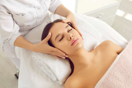 Close up top view of dermatologist do face lifting massage for female patient in beauty clinic. Cosmetologist make skincare facial procedures treatment for woman client in salon. Cosmetology concept.