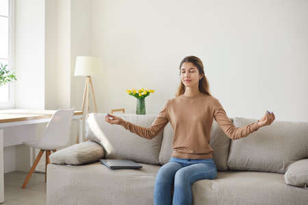 Calm girl resting on soft comfortable sofa meditates enjoying stress-free peaceful weekend without stress. Carefree young woman spends day in living room relaxing on sofa at home. Leisure concept.