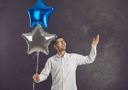 Happy man with cheerful positive face expression holding pair of balloons for birthday party. Portrait of smiling young guy in shirt and glasses with two shiny balloons standing on grey background