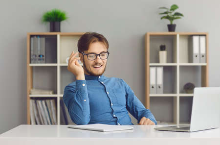 Smiling millennial Caucasian man speak talk on video call on computer in office. Happy young male employee trainer have webcam virtual digital online event on laptop. Communication concept. Standard-Bild