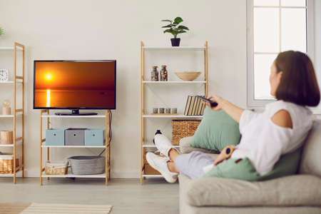 Relaxed woman sitting on couch and watching her favourite TV show. Happy adult lady resting on sofa and enjoying good film on modern television set with big HD screen