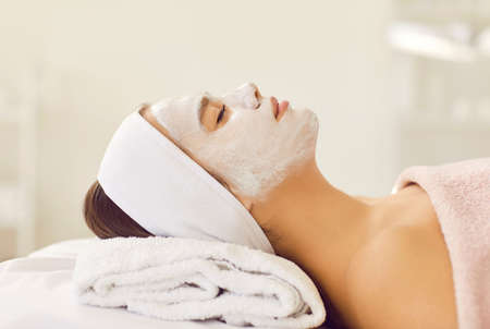 Professional cosmetology and treatment. Beautiful woman with headband and cleansing white mask on her face relaxes in spa or beauty salon. Side view close up of woman with closed eyes lying on towel.
