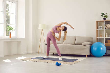 Fit active millennial girl in sportswear do morning gymnastics exercise train at home on lockdown. Sporty toned young Caucasian woman follow healthy lifestyle workout alone. Sport, fitness concept. Standard-Bild