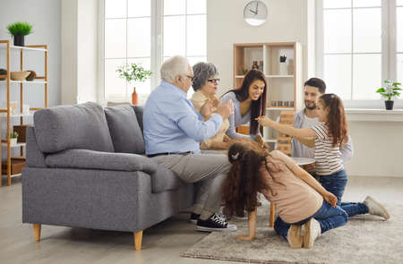 Grandparents come to visit. Happy multi generational family playing board game at home. Mom, dad, granny, granddad, children gather in modern living room, build tumble tower, enjoy good time together