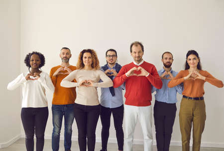 Team of happy multiracial youth and old citizens sending you love, support and gratitude. Studio group portrait of thankful young and mature people standing together and doing heart shape hand gesture