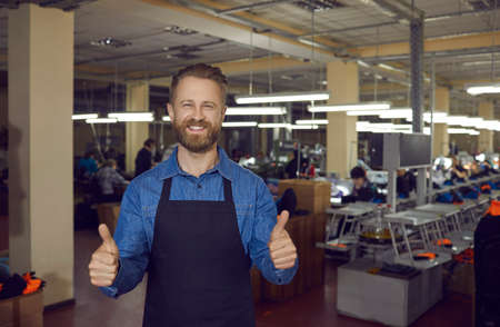 Confident happy male worker or owner of clothing and footwear factory showing cool gesture guaranteeing product quality. Adult bearded man shows thumbs up while standing in a large workshop.