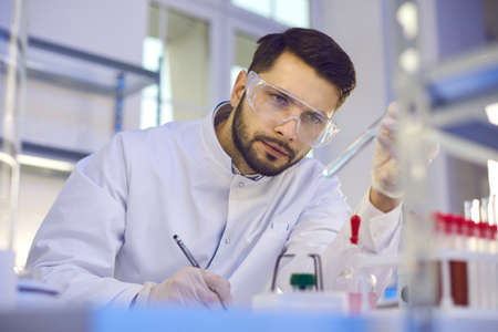 Close up of a focused male scientist looking at a test tube with liquid in his hand and writing down the results of the study. Man is working on the development of a new drug in a medical laboratory.