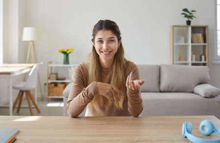 Laptop computer screen view of happy beautiful young woman sitting at work desk in home office in living room, gesturing and talking to friend or colleague during casual online meeting via video call