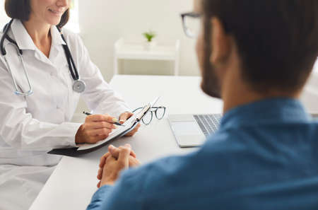 Woman who works as physician sitting at desk, talking to young man, writing down patients prescription, giving advice and recommendations. Consultation at doctors office, clinic, or hospital concept Standard-Bild
