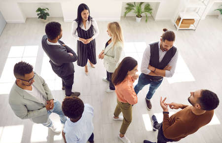 Groups of multi ethnic people standing in office and talking. Diverse men and women communicating during casual corporate meeting, psychological training or after business event. High angle shot
