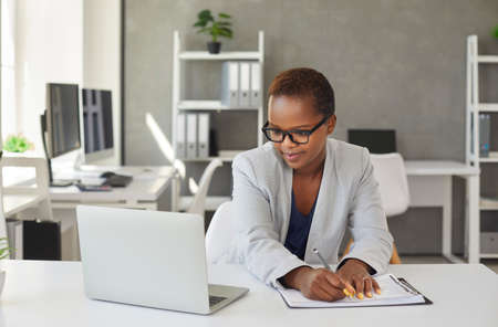 Serious focused concentrated young black woman in stylish suit and spectacles sitting at office desk, working on business project report, looking at screen of laptop computer, taking important notes